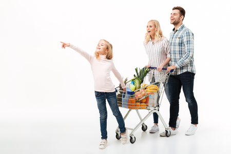 Photo pour Full length portrait of a young family walking with a shopping trolley full of groceries isolated over white background - image libre de droit