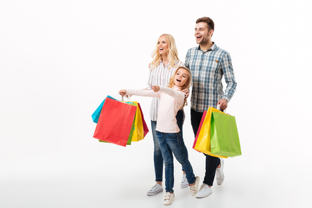 Foto de Full length portrait of a cheerful family holding paper shopping bags while walking isolated over white background - Imagen libre de derechos