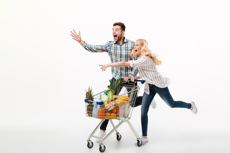 Photo pour Full length portrait of an excited couple running with a supermarket trolley and pointing fingers isolated over white background - image libre de droit