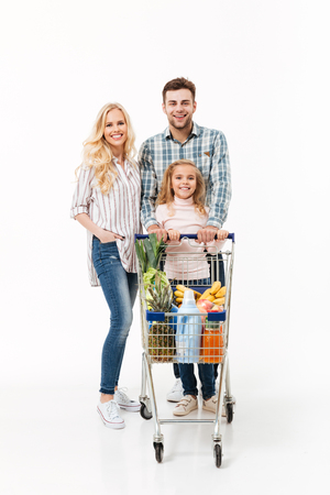Photo pour Full length portrait of a cheerful family standing with a shopping trolley full of groceries isolated over white background - image libre de droit