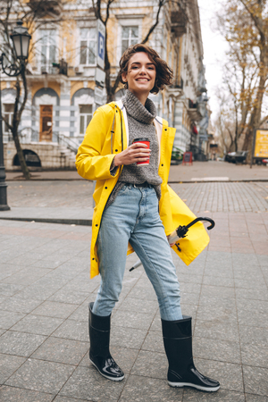 Photo pour Photo of cheerful pretty young woman dressed in rubber boots and yellow raincoat walking outdoors drinking coffee. Looking camera. - image libre de droit