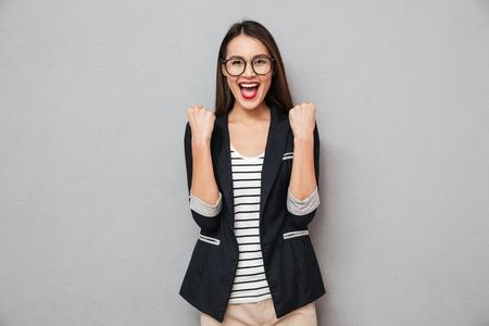 Foto de Happy screaming asian business woman in eyeglasses rejoices and looking at the camera over gray background - Imagen libre de derechos