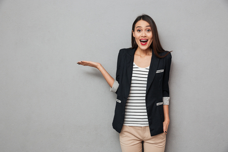 Photo pour Surprised happy asian business woman holding copyspace on the palm and looking at the camera over gray background - image libre de droit