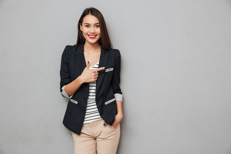 Photo for Smiling asian business woman with arm in pocket pointing away and looking at the camera over gray background - Royalty Free Image