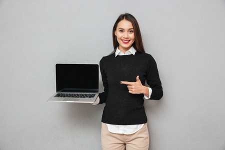 Photo pour Pleased asian woman in business clothes showing blank laptop computer screen and pointing on it while looking at the camera over gray background - image libre de droit