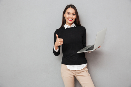 Foto de Pleased asian woman in business clothes holding laptop computer and showing thumb up while looking at the camera over gray background - Imagen libre de derechos