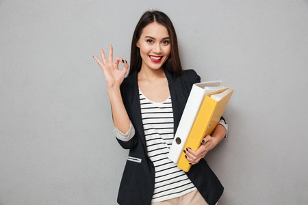 Photo for Smiling asian business woman holding folders and showing ok sign while looking at the camera over gray background - Royalty Free Image