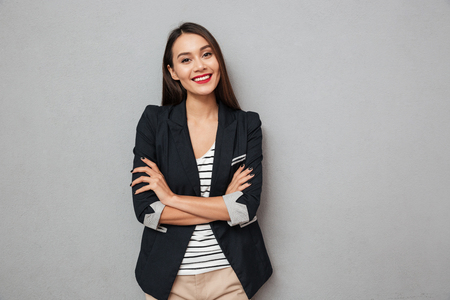 Photo pour Pleased asian business woman with crossed arms looking at the camera over gray background - image libre de droit