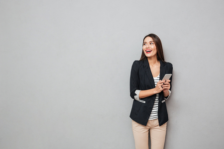 Foto de Cheerful asian business woman holding smartphone and looking away over gray background - Imagen libre de derechos