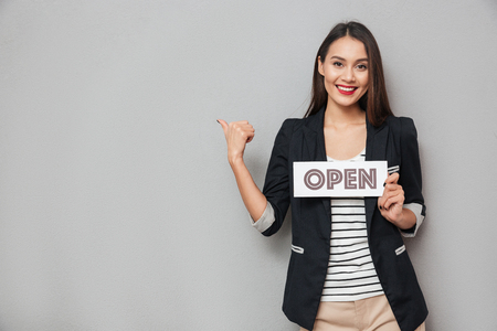 Photo pour Pleased asian business woman holding nameplate open and pointing on copyspace while looking at the camera over gray background - image libre de droit