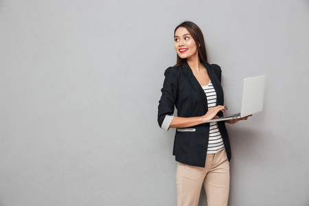 Foto de Smiling asian business woman holding laptop computer and looking back over gray background - Imagen libre de derechos