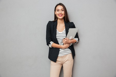 Foto de Pleased asian business woman holding laptop computer and looking at the camera over gray background - Imagen libre de derechos
