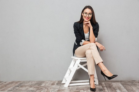 Photo for Smiling asian business woman in eyeglasses sitting on chair and looking at the camera over gray background - Royalty Free Image