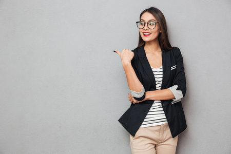 Photo pour Smiling asian business woman in eyeglasses pointing and looking away over gray background - image libre de droit
