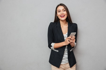 Foto de Happy asian business woman holding smartphone and looking at the camera over gray background - Imagen libre de derechos