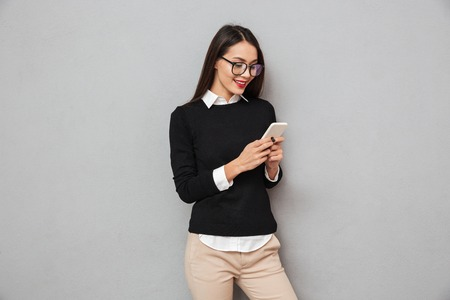 Foto de Smiling asian woman in business clothes and eyeglasses writing message on smartphone over gray background - Imagen libre de derechos