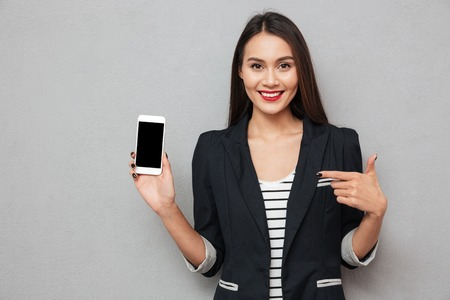 Foto de Smiling asian business woman showing blank smartphone screen and pointing on him while looking at the camera over gray background - Imagen libre de derechos