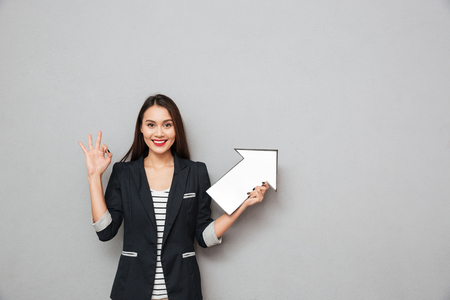 Photo for Smiling asian business woman showing ok sign and pointing with paper arrow up while looking at the camera over gray background - Royalty Free Image