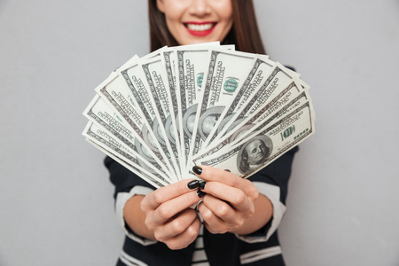 Foto de Cropped image of smiling asian business woman showing money at the camera over gray background - Imagen libre de derechos