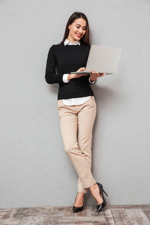 Photo for Full length image of Smiling asian woman in business clothes using laptop computer over gray background - Royalty Free Image