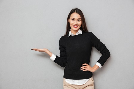 Foto de Smiling asian woman in business clothes with arm on hip holding copyspace on the palm while looking at the camera over gray background - Imagen libre de derechos