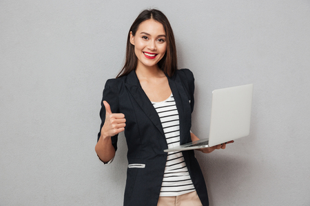 Photo pour Holding asian business woman holding laptop computer and showing thumb up while looking at the camera over gray background - image libre de droit