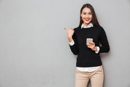 Foto de Smiling asian woman in business clothes holding smartphone and pointing on copyspace while looking at the camera over gray background - Imagen libre de derechos