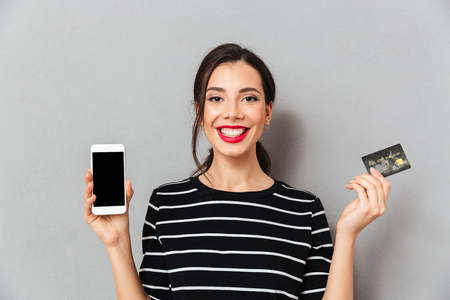 Photo for Portrait of a cheerful woman showing blank screen mobile phone and a credit card isolated over gray background - Royalty Free Image