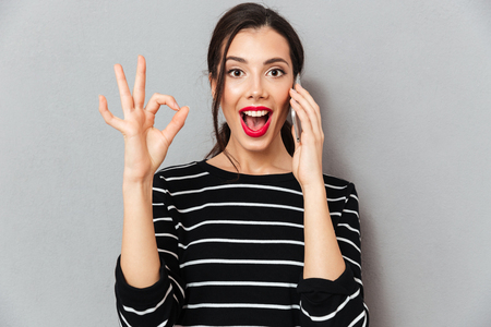 Foto de Portrait of an excited woman talking on mobile phone and showing ok gesture isolated over gray background - Imagen libre de derechos