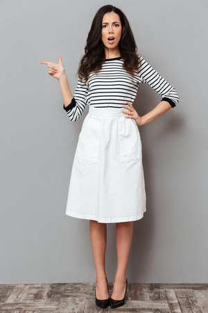 Foto de Full length portrait of a frowning woman dressed in a skirt standing and pointing finger away at copy space isolated over gray background - Imagen libre de derechos