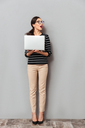 Photo for Full length portrait of a surprised woman in eyeglasses holding laptop computer and looking away at copy space isolated over gray background - Royalty Free Image