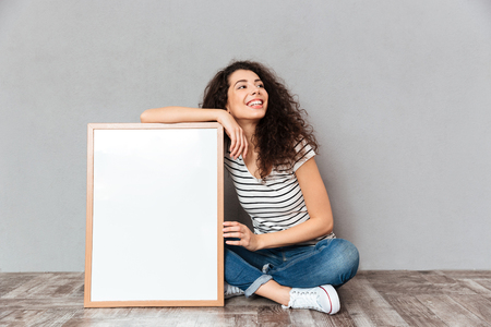 Foto de Caucasian woman with beautiful hair posing with legs crossed demonstrating big great painting or portrait, isolated over grey wall copy space - Imagen libre de derechos