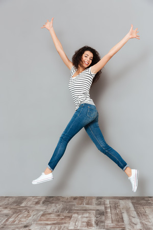 Photo for Energetic woman 20s in striped t-shirt and jeans, jumping with hands throwing up in air over grey background - Royalty Free Image