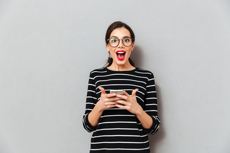 Photo pour Portrait of a happy woman in eyeglasses holding mobile phone and looking at camera isolated over gray background - image libre de droit