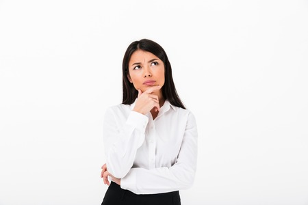 Foto de Portrait of a pensive asian businesswoman thinking and looking away at copy space isolated over white background - Imagen libre de derechos