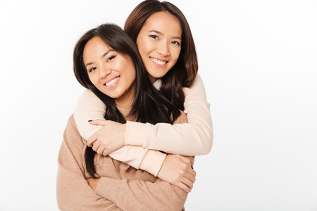 Foto de Image of two asian pretty cheerful ladies sisters hugging with each other. Looking camera. - Imagen libre de derechos