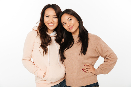 Photo pour Image of two asian pretty cheerful ladies sisters hugging with each other. Looking camera. - image libre de droit