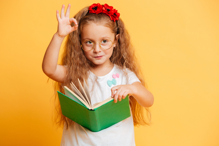 Photo for Image of little cute pretty girl standing isolated over yellow background wearing glasses looking aside reading book showing okay gesture. - Royalty Free Image