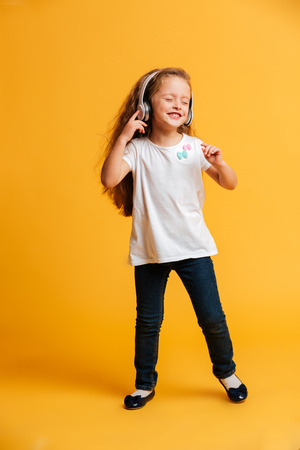 Photo pour Photo of little girl dancing isolated over yellow background listening music with headphones. Eyes closed. - image libre de droit