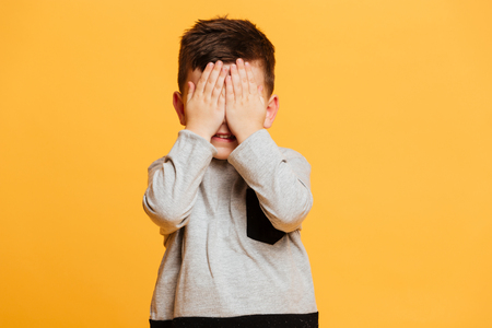 Photo pour Image of little boy child standing isolated over yellow background covering eyes with hands. - image libre de droit