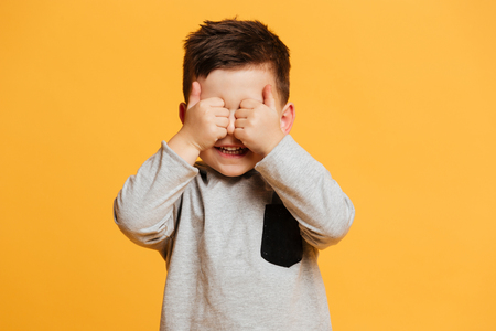 Photo pour Picture of smiling cute little boy child standing isolated over yellow background showing thumbs up covering eyes. - image libre de droit