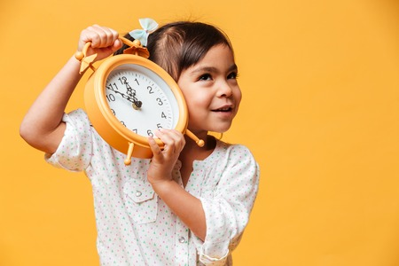 Photo pour Photo of cheerful little girl child standing isolated over yellow background holding clock alarm. - image libre de droit