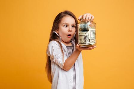 Foto de Photo of shocked little girl child standing isolated over yellow background holding jar with money. - Imagen libre de derechos