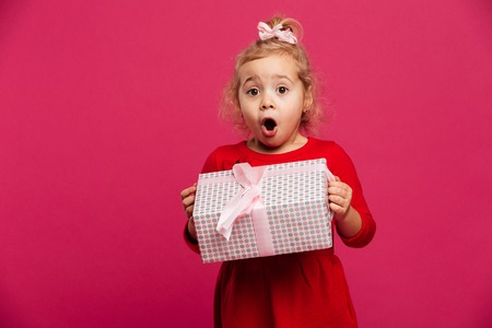 Photo for Shocked young blonde girl in red dress holding gift box and looking at the camera over pink background - Royalty Free Image