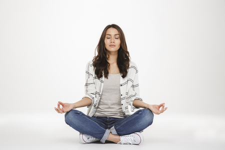 Foto de Full-length picture of concentrated woman in casual clothes meditating with closed eyes while sitting in lotus pose on the floor isolated over white wall - Imagen libre de derechos