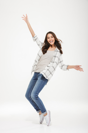 Photo pour Full length image of Happy brunette woman in shirt having fun and looking at the camera over gray background - image libre de droit