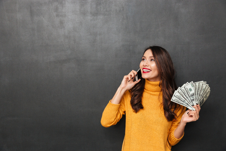 Foto de Smiling brunette woman in sweater holding money and talking by smartphone while looking away over black background - Imagen libre de derechos