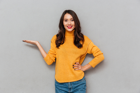 Photo pour Pleased brunette woman in sweater with arm on hip holding copyspace on the palm and looking at the camera over gray background - image libre de droit