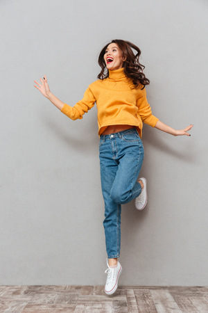 Photo pour Full length image of Happy brunette woman in sweater jumping and looking away over gray background - image libre de droit
