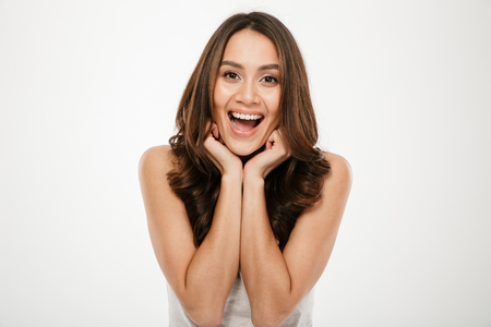 Foto de Picture of Joyful brunette woman posing and looking at the camera over gray background - Imagen libre de derechos